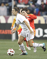 Yael Averbuch #4 of the USA WNT moves past Danyang Li #14 during an international friendly match against the PRC WNT at PPL Park, on October 6 2010 in Chester, PA. The game ended in a 1-1 tie.