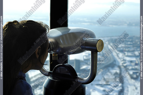 Young woman looking through binoculars Enjoying Toronto city view from CN tower Travel tourism and sightseeing concept