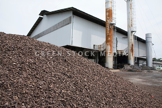 A large pile of oil palm kernel shells left over from the milling process. Some of the shells are combined with pressed palm fiber as a biofuel to generate the mill's electricity via a steam turbine. The Sindora Palm Oil Mill, owned by Kulim, is green certified by the Roundtable on Sustainable Palm Oil (RSPO) for its environmental, economic, and socially sustainable practices. Johor Bahru, Malaysia