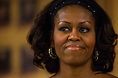 First lady Michelle Obama listens as her husband, United States President Barack Obama, speaks to members of the U.S. military and their families as they eat a Christmas Day meal in the Anderson Hall mess hall at Marine Corps Base Hawaii at Kaneohe Bay in Kaneohe, Hawaii, USA, on 25 December 2013. <br /> Credit: Kent Nishimura / Pool via CNP