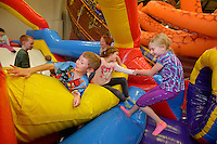 STAFF PHOTO BEN GOFF  @NWABenGoff -- 12/05/14 Elijah Hall, 7, left, scales an inflatable obstacle as his sister Abigail Hall, 10, right, helps friend Madison Dunn, 8, get over while playing at Jump!Zone Party Play Center in Bentonville on Friday Dec. 5, 2014. The children were visiting with a group of home-schooled friends from Bentonville and Rogers.