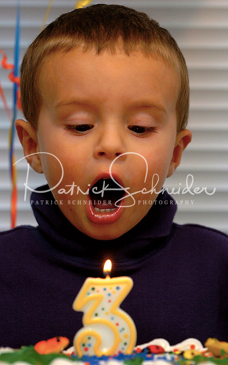 A young boy celebrates his third birthday with a candle and cake.
