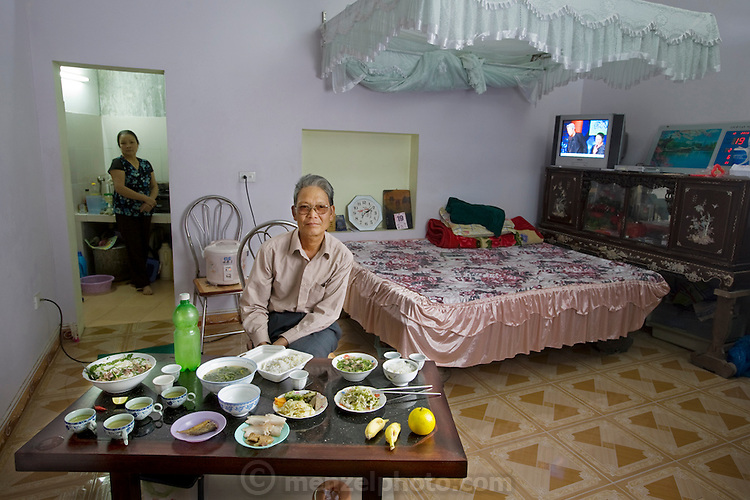 Nguyên Van Thuan, a war veteran, with his wife in their studio apartment with his typical day's worth of food. (From the book What I Eat: Around the World in 80 Diets.) MODEL RELEASED.