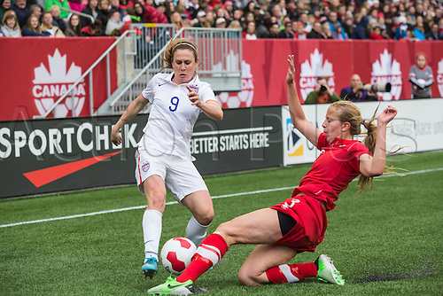 08.05.2014. Manitoba, Canada.  Team USA's Heather O'Reilly (9) is stopped by Team Canada's Rebecca Quinn (3) during the USA versus  Canada game at the Investors Group Field in Winnipeg MB.
