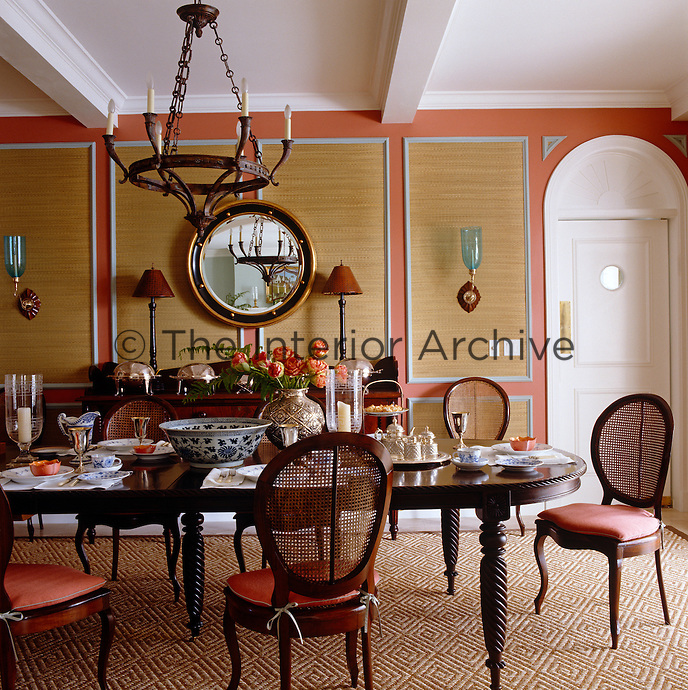 The long dining room table is laid for tea and is surrounded by antique cane-backed chairs with seat cushions in burnt orange to match the walls