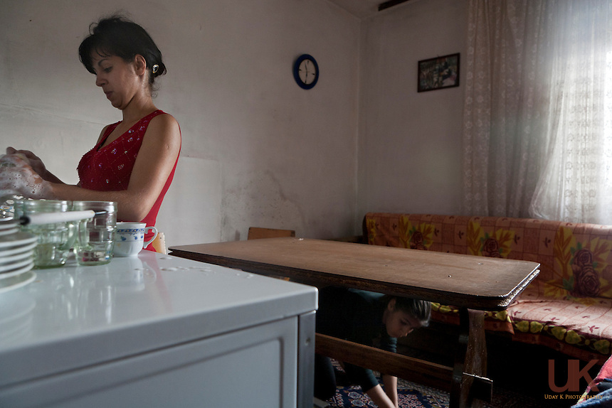 Dina does the dishes and Endriana sweeps the carpet. Woman end up doing all the house chores in a typical Roma family.