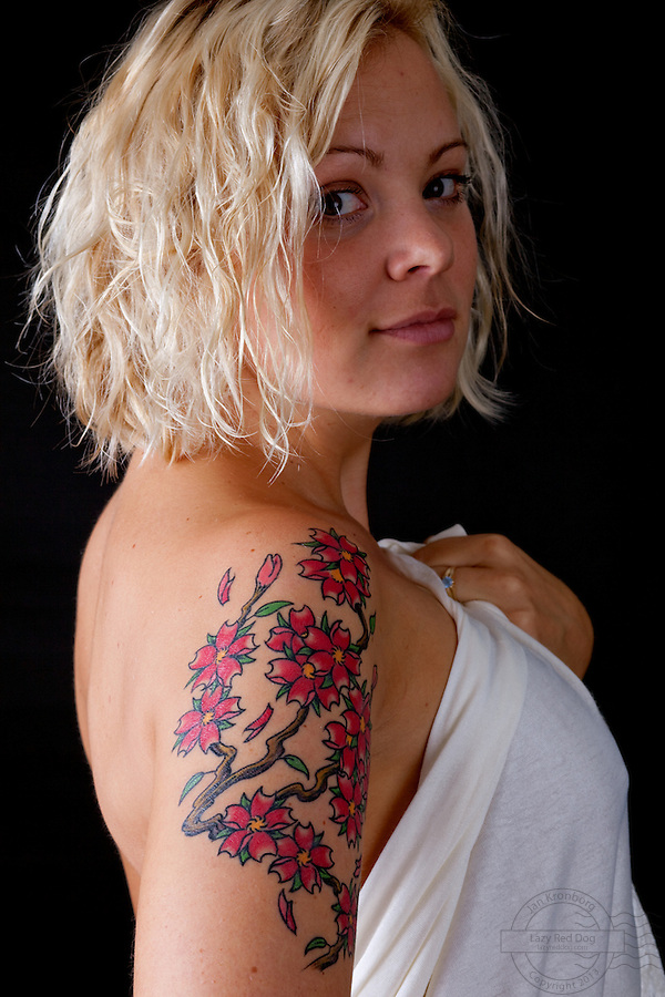 Tattoos on a young danish woman. All tattooed at the Miss Roxy studio in Copenhagen except for the most recent on her upper arm. The cherry blossoms where done by Alex at Rite of Passage located in copenhagen. The tattoos all symbolise personal issues like friendship and personal development.