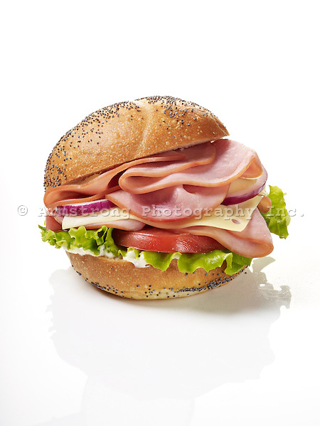 A sandwich with sliced ham, tomatoes, lettuce, and mayonnaise on a poppy seed kaiser roll. On a white background.
