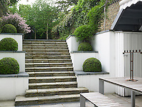 A flight of stone steps flanked by a series of planted terraces leads up from the patio at the rear of the house