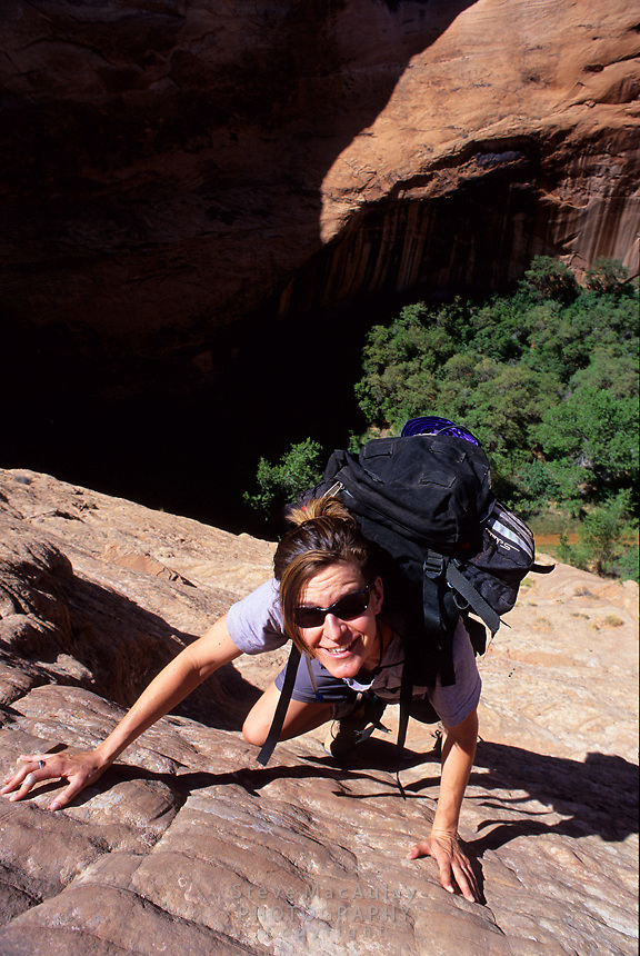 Female backpacker climbing the very steep and exposed exit from Coyote Gulch at Jacob Hamblin Arch, Grand Staircase Escalante National Monument, Utah