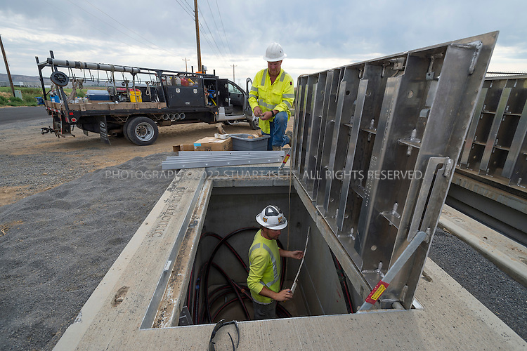 8/21/2012--Quincy, WA..Bob Bond (standing) and Travis Maiuri (below), working for subcontractor Potelco, work on power lines being run from a Grant County PUD substation to a Sabey data center center being built just up the road in Quincy, WASH. ..Quincy has seen rapid growth of data centers, or server farms, spurred on by tax rates and low cost electricity produced by the Grant Count PUD's nearby hydroelectric dams. Microsoft and five other companies, including Yahoo and Dell, have brought big, energy-hungry data centers to Quincy in recent years, converting former bean fields into vital hubs on the internet...©2012 Stuart Isett. All rights reserved.