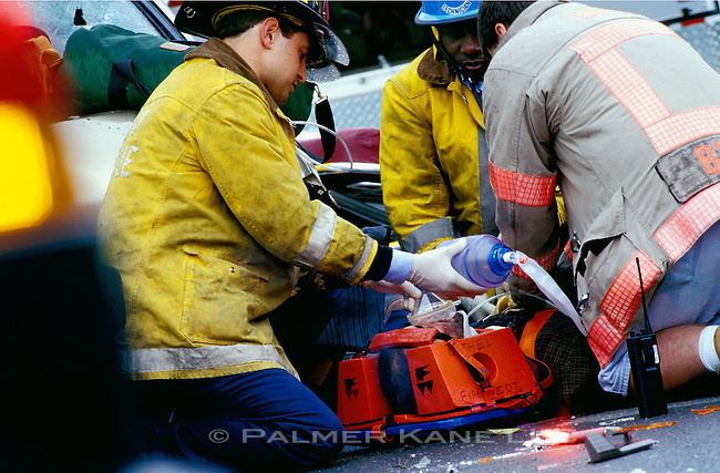 Paramedics and rescue worker tend to critically injured victim after an automobile accident.