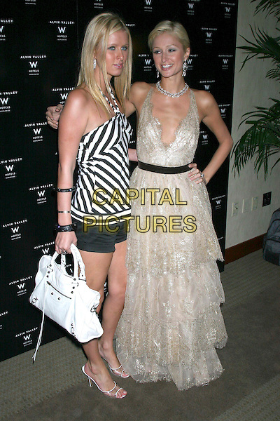 NICKY HILTON & PARIS HILTON.Olympus Fashion Week Spring 2006.Albin Valley, New York, 12th September 2005.full length black white stripe halter neck strap top hotpants shorts sandals purse handbag lace layer chiffon dress silver earrings hand hip sisters.Ref: IW.www.capitalpictures.com.sales@capitalpictures.com.©Capital Pictures