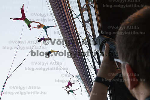 Photographer takes pictures as members of the Bandaloop company from USA perform on the glass wall of an office building during the the CAFe Contemporary Art Festival in downtown Budapest, Hungary on Oct. 20, 2017. ATTILA VOLGYI