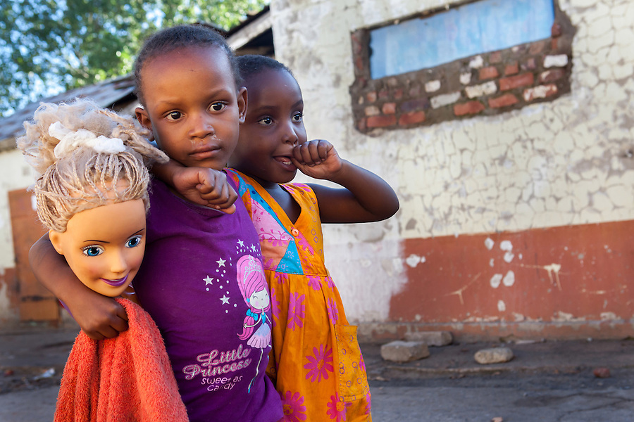 """I photographed these two little girls and a doll's head at Durban Deep's old """"Skomplaas"""" hostel. While the gold mine was still operating, the hostel housed hundreds of goldminers. Today a large number of families live in the crumbling buildings in very poor sanitary conditions. Having grown up in South Africa during the apartheid era, I did not miss the irony of the white disembodied doll's head. Despite the fact that apartheid ended more than 20 years ago, the country is still haunted by its apartheid past."""