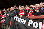 Home fans at Broadhurst Park, Manchester, the new home of FC United of Manchester during the first-half of the club's match against Benfica, champions of Portugal, which marked the official opening of their new stadium. FC United Manchester were formed in 2005 by fans disillusioned by the takeover of Manchester United by the Glazer family from America. The club gained several promotions and played in National League North in the 2015-16 season, but lost this match 1-0.