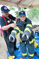 Fireman dressing boy age 11 in firefighters gear at rescue demonstration. Aquatennial Beach Bash Minneapolis Minnesota USA