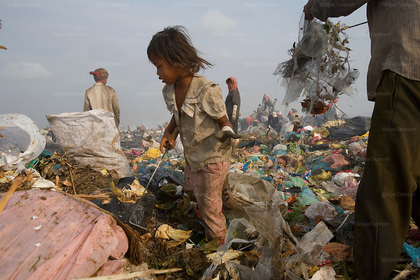 RUBBISH DUMP RECYCLING. South East Asia, Cambodia, Phnom Penh. Smokey Mountain, Steung Mean Chey, is Phnom Penh's municipal rubbish dump. Thousands work there, some 600 minors and 2000 adults, recycling the city's rubbish, dumped there by garbage trucks every day. The dump is notorious as many very young children work there. People eat and sleep overnight in the rubbish and fumes, under plastic tarpaulins or in the open air. They work 24 hours a day, like miners, with headlamps at night, collecting plastic, metals, wood, cloth & paper, which they sort and clean, weigh and sell, to be carried away for recycling. A day's work typically brings less than a dollar per person. One and a half to two dollars per day per family. The overpowering, acrid odour of grey smokey fumes blows across the dump, from which the place gets its name 'Smokey Mountain'. It can be smelt miles away. The shantytowns and squats, the recycling worker's homes butt onto or are inside the dump itself. There is no running water, sanitation and many are ill. Children often work with friends or relatives. Religious and ngo's help some children, but this is often resisted by families who need the extra income they generate.///Sitay, aged 8 years, is the sole earner for her family. She works with her mother's friends. Her mother is ill and her father dead. They live in a squat inside the rubbish dump, unable to afford rent.
