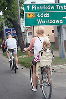 Polish family bicycling thru town with child in rear seat. Tomaszow Mazowiecki Central Poland