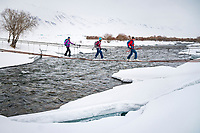Skiers crossing a bridge over a river while ski touring in the Suusamyr region of Kyrgyzstan