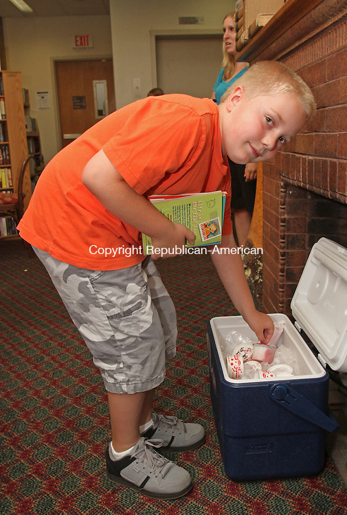 Winsted, CT-071815MK12 Vincent Carpenter gets ready to enjoy a frozen treat after he checked out some books at the Beardsley and Memorial Library in Winsted Saturday afternoon.  Linda Gordon, program coordinator, said there was a selection of 100 items of ice cream, popsicles or frozen ices for children as well as adults to choose from.  The activity was held to celebrate national ice cream day, which is today, with those patrons who borrowed books or participated in the library's presentations.   Michael Kabelka / Republican-American