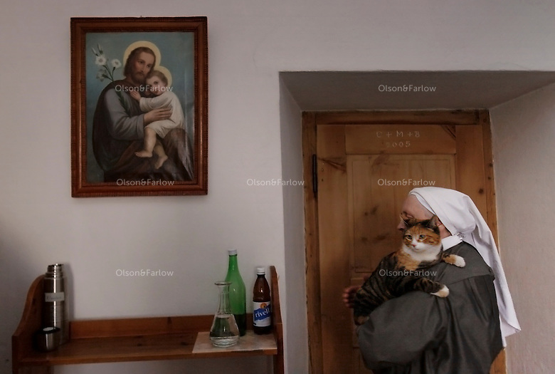 A nun carries a cat that slipped into the living quarters of the convent at Val Mustiar near Italy.<br /> <br /> Val Mustiar is a world-famous Benedictine Convent of St. John, which is a UNESCO World Heritage Site.  The alpine monastery was founded by Charlemagne, was built in the 8th centruy, the church houses the world's richest and best preserved series of figuratives Romanesque murals with impressive Carolingian frescos..Since the 12th century the monastery is run by Benedictine nuns.  Eleven make their home behind closed walls, living a life of commitment to poverty and celebacy.  Each nun has her work and they come together for prayer and meals.The nuns speak a variation of the Romanche language. The dialect changes from valley to valley from Mustair to St. Moritz.