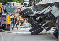 NWA Democrat-Gazette/ANTHONY REYES • @NWATONYR<br /> Logan Skaggs, with Decatur Salvage and Wrecker, rolls an 18-wheeler upright Wednesday, Sept. 9, 2015 on Highway 72 in Centerton. The 18-wheeler, which was hauling a load of gravel, was traveling east on Highway 72 when it failed to properly handle and turn and rolled onto its side. Much of the load was thrown down the embankment south of the highway. There were no injuries in the accident.
