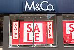 M & Co store sale posters in shop window, Woodbridge, Suffolk, England, UK