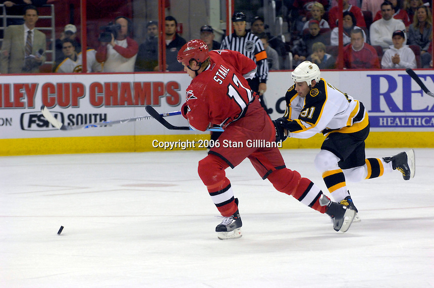 The Boston Bruins' Marc Savard (91) races the Carolina Hurricanes' Eric Staal (12) for a puck during an NHL hockey game Saturday, Dec. 2, 2006 in Raleigh, N.C. Carolina won 5-2.<br />