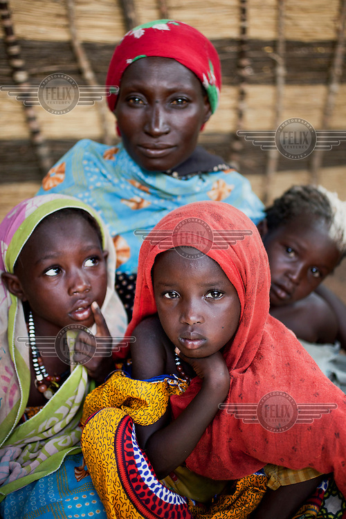 A woman sits with her children in the village of Luga. Across the Sahel drought, exacerbated by a rise in global food prices, has left about 40% of Niger's population facing severe food insecurity. This particularly affects women and children with an estimated 127,000 children under five years old predicted to suffer from severe malnutrition during 2012.