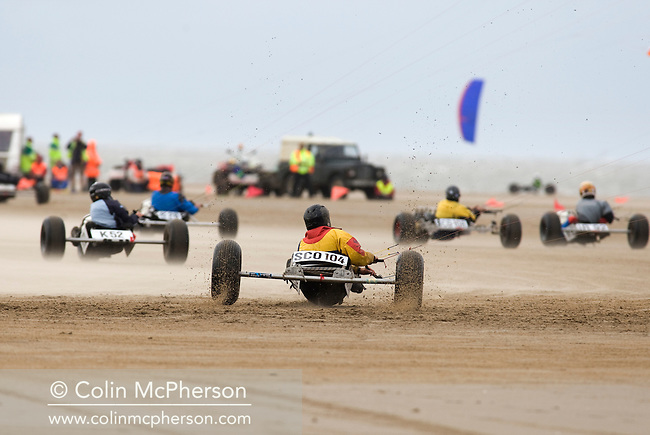 Two competitors taking part in one of the races at the European Kite Buggy Championships at Hoylake, Wirral, north west England. Around 75 buggies, with both male and female pilots, from 10 countries took part in the annual event which lasted from 5-9 September 2011. The three-wheeled, single-seated, steel frame buggy was powered  by a traction, or power kite and could achieve speeds of up to 70mph/110km/h.