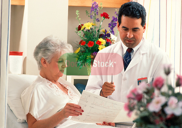 doctor discussing and showing test results with oldery woman patient in hospital bed