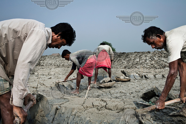 Casual labourers with the family name Chowduli building fish ponds. Chowduli is a Muslim name and, although not part of the Hindu caste system, among Muslims they are stigmatised and the name is synonymous with low status. Consequently the West Bengal government has bestowed on them the status of 'backward'. This entitles them to positive discrimination when applying for government jobs and education.