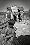 A yung monk adjusts his flowing robe at Angkor Wat Temple, Cambodia