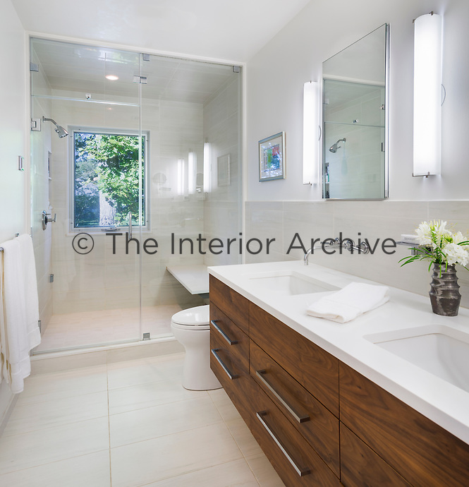 A modern, part tiled white bathroom with two washbasins set in a wood drawer unit. At one end is an enclosed shower room.