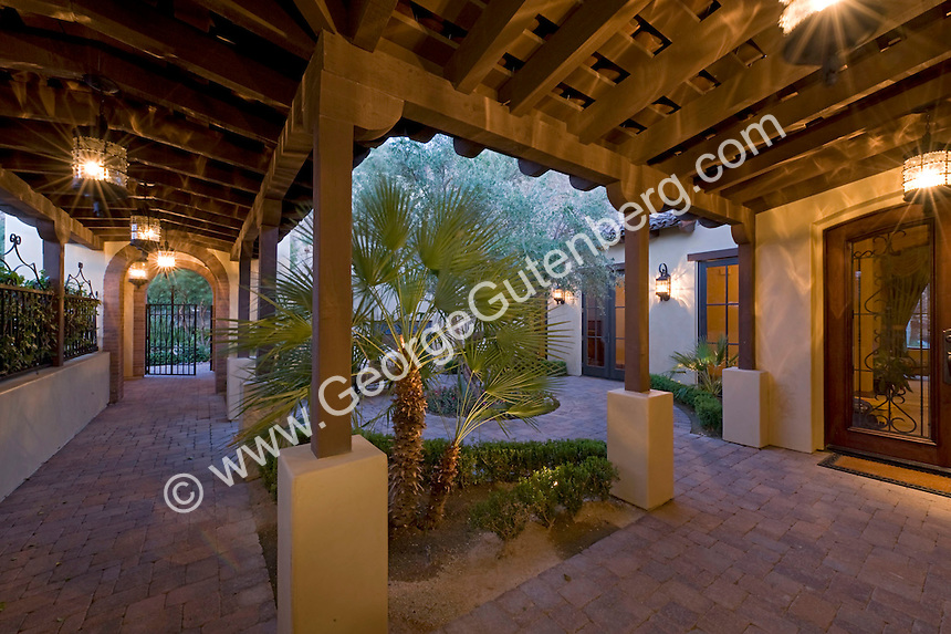 Tuscan house courtyard with palm tree and brick walkway