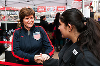 former women's national team player April Heinrichs shakes hands with a fan during the centennial celebration of U. S. Soccer at Times Square in New York, NY, on April 04, 2013.