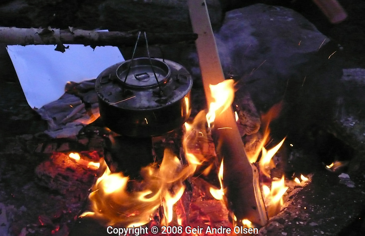 Campfire and old coffeepot at hiking-trip in the Norwegian Forrest this fall