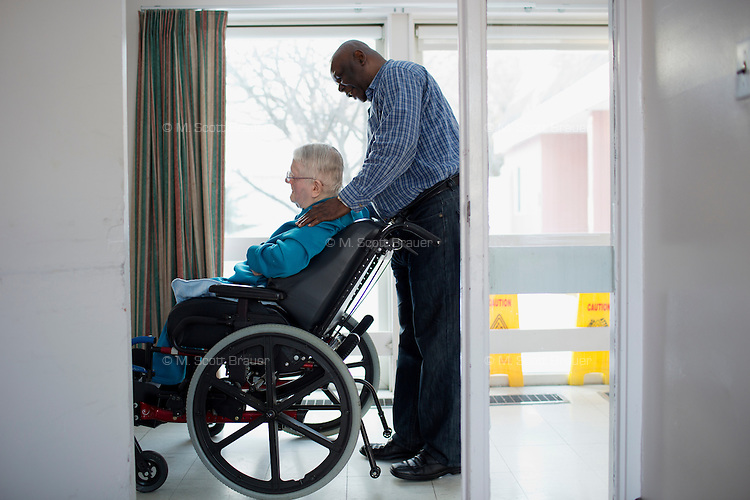 Caregiver Jean Castor pushes resident Margaret Rouleau, 84, down a hallway in her residence at Malone Park at the Fernald Center in Waltham, Massachusetts, USA.  Margaret is one of the few residents who can speak.