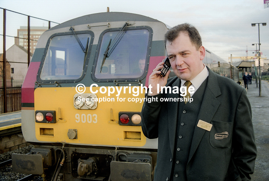 David Grant, a Translink manager, in front of a Belfast to Dublin Enterprise tractor unit at Belfast Central Station, N Ireland, January, 2000, 200001001DG<br /> <br /> Copyright Image from Victor Patterson, 54 Dorchester Park, <br /> Belfast, UK, BT9 6RJ<br /> <br /> t1: +44 28 9066 1296 (from Rep of Ireland 048 9066 1296)<br /> t2: +44 28 9002 2446 (from Rep of Ireland 048 9002 2446)<br /> m: +44 7802 353836<br /> <br /> e1: victorpatterson@me.com<br /> e2: victorpatterson@gmail.com<br /> <br /> www.victorpatterson.com<br /> <br /> Please see my Terms and Conditions of Use at VICTORPATTERSON.COM. It is IMPORTANT that you familiarise yourself with them.<br /> <br /> Images used on the Internet must be visibly watermarked i.e. &copy;VICTORPATTERSON.COM within the body of the image and copyright metadata must not be deleted. Images used on the Internet have a size restriction of 4kbs and are chargeable at the then current NUJ rates.<br /> <br /> This image is only available for the use of the download recipient i.e. television station, newspaper, magazine, book publisher, etc, and must not be passed on to any third party. It is also downloaded on condition that each and every usage is notified within 7 days to victorpatterson@me.com<br /> <br /> The right of Victor Patterson to be identified as the author is asserted in accordance with The Copyright Designs And Patents Act (1988).