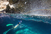 A woman snorkels in a cave at Shark's Cove (or Sharks Cove) on the North Shore of O'ahu.