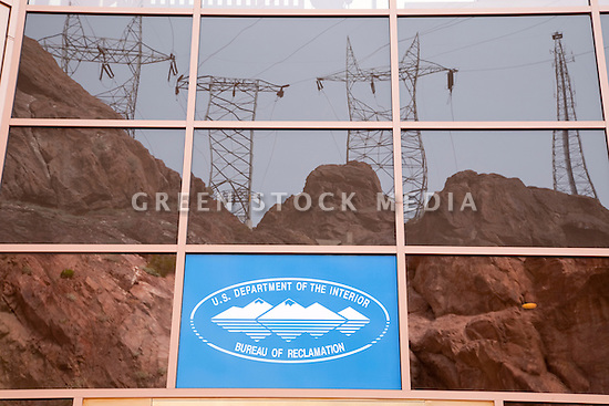 Power lines are reflected in the tinted windows of the Bureau of Reclamation's visitor center at Hoover Dam. Hoover Dam spans the Colorado River at the border between Nevada and Arizona. Lake Mead is the reservoir behind the dam. The dam's hydroelectric power station generates, on average, about 4 billion kilowatt-hours of power a year and is distributed to Nevada, Arizona, and California. It meets the energy needs of approximately 1.3 million people. Lake Mead is also a significant source of municipal drinking water and agricultural water for the region. Almost a decade of drought and increased water demand have brought Lake Mead near its lowest level in over 40 years. Photo taken February 2009.