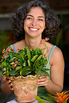 Mature woman in garden holding potted plant, smiling, portrait
