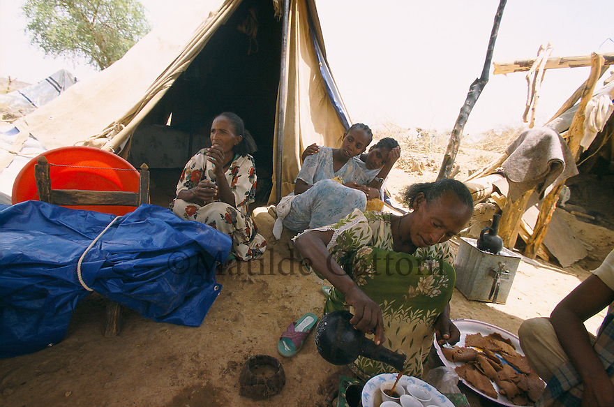 Eritrea - Debub- Family sitting under their tent in an IDP camp. As a result of 30 years of war for independence against Ethiopia (from 1961 to 1991) and another 3 years from 1997 to 2000, there are 50,000 Eritreans currently living in internally displaced (IDP) camps throughout the country. These IDPs have fled three times in the last 10 years, each time because of renewed military conflict. They lived in relatives' homes when lucky enough, but mostly, the fled to the mountains, where they attempted to do what Eritreans do best, survive. Currently there is no Ethiopian occupation in Eritrea, but landmines prevent the IDPs from finally going home. .It is estimated that every Eritrean family lost two or three members to the war which makes the reality of the current emergency situation even more painful for Eritreans worldwide. Currently, the male population has been decreased dramatically, affecting the most fundamental socio-economic systems in the country. Among the refugee population, an overwhelming majority of families are female-headed, severely affecting agricultural production. For, IDPs in particular, 80% of households are female-headed..The unresolved border dispute with Ethiopia remains the most important drawback to Eritrea's socio-economic development, as national resources (human and material) continue to be prioritized for national defense. Eritrea is vulnerable to recurrent droughts and variable weather conditions with potentially negative effects on the 80 percent of the population that depend on agriculture and pastoralism as main sources of livelihood. The situation has been exacerbated by the unresolved border dispute, resulting in economic stagnation, lack of food security and increased susceptibility of the population to various ailments including communicable diseases and malnutrition..