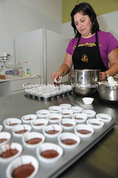 WATERBURY, CT 24 SEPTEMBER 2013--092413JS05-Lynne Fascia Movanes, owner of Lynne's Chocolate Cakery, makes mini cupcakes on Tuesday inside Fascia's Chocolates'  new 12,500 square-foot facility on Chase River Road in Waterbury on Tuesday. The new location includes space for tours and corporate meetings. <br /> Jim Shannon Republican American