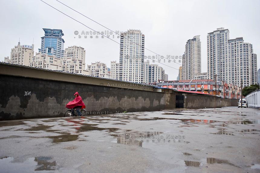 Un uomo in bicicletta in una zona della citt&agrave; ad elevata densit&agrave; abitativa.<br /> Shanghai is the largest Chinese city by population and the largest city proper by population in the world.