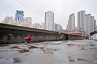 Un uomo in bicicletta in una zona della città ad elevata densità abitativa.<br /> Shanghai is the largest Chinese city by population and the largest city proper by population in the world.