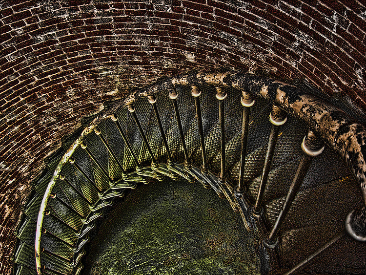A photograph of a metal stairs in a brick lighthouse in Oregon manipulated by creator to accentuate the threat represented by decending tightly constructed, circular staircases predominately found in lighthouses. Best printed on metallic finished paper. Selected for Photographic Center - Capital District - 2010 Members' Show.