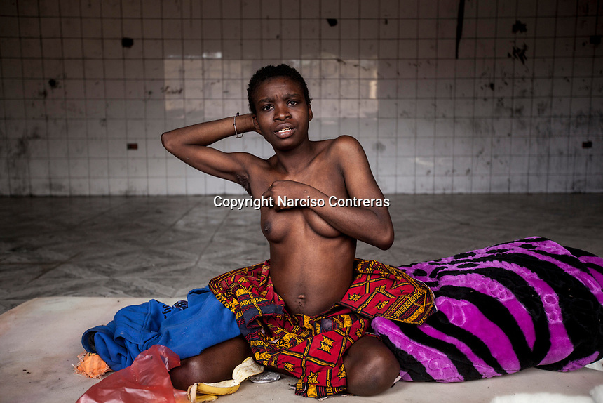 An unidentified mentally ill Sub-Saharan illegal migrant strips inside an isolated cell in a Surman detention center, revealing an abortion scar on her belly. A local doctor says that the woman, presumably a rape victim, has been detained for the last two years. When asked about the woman's scar he replies that it is unclear if she became pregnant whilst in custody, or beforehand.