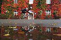 16/10/16 <br /> <br /> After heavy overnight rain, a cyclist rides past stunning autumnal colours on a Boston Ivy Vine (or Japanese Creeper) that are reflected in puddles outside the The Old Eyre Arms in Hassop, near Bakewell in the Derbyshire Peak District. <br /> <br /> All Rights Reserved: F Stop Press Ltd. +44(0)1773 550665   www.fstoppress.com